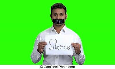 Censored man holding card with inscription Silence. Chroma...