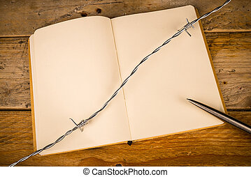 Censorship - Notebook and pen with barbed wire, a press ...