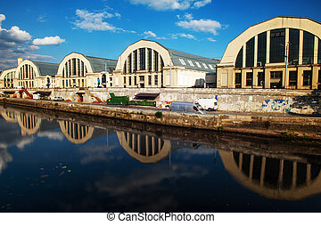 Central Market in Riga in Latvia reflecting in water. It was built in 1920s and is coinsidered as the largest marketplace in Europe. It was included to UNESCO list in 1998