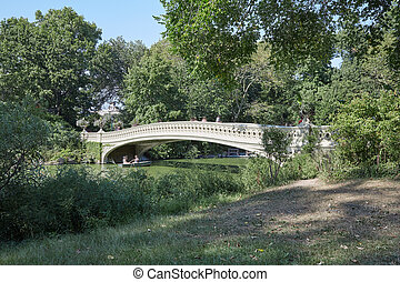 Central Park and white bow bridge with people in a sunny day in New York