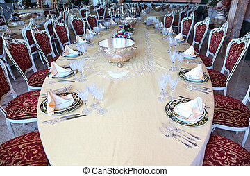 Centre of big oval dinner table with candlestick, copper and empty dishes: plates with placemat, forks, knives and goblets