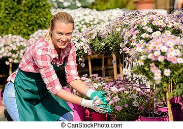 centro jardim, mulher, margarida, flores potted, sorrindo