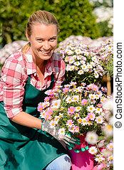 centro jardim, mulher segura, flores potted, sorrindo