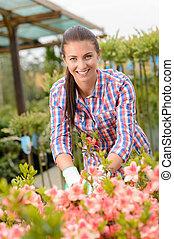 centro jardim, mulher, trabalhando, em, flowerbed, sorrindo