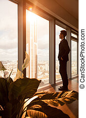 CEO dreaming of success while looking at window