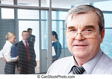 Ceo - Portrait of mature boss in eyeglasses looking at...