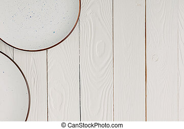 Ceramic beautiful plates on white wooden background