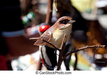 ceramic bird on a branch at the fair