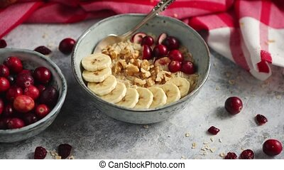 Ceramic bowl of oatmeal porridge with banana, fresh...