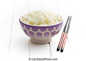 ceramic bowl with jasmine rice and chopsticks