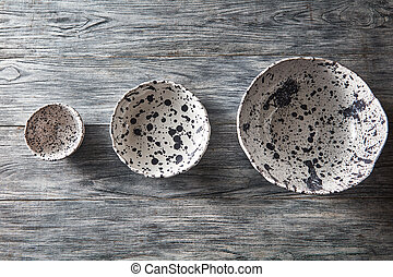 Ceramic bowls of different sizes are empty on a gray wooden...