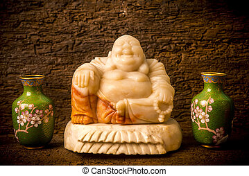 Ceramic Buddha Hotey figurine between vases on shelf