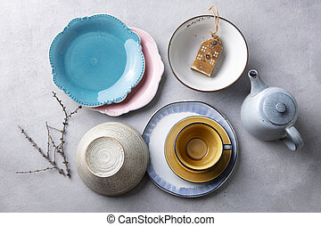 Ceramic crockery tableware, plates, bowls, cup and teapot on grey stone background. Top view.