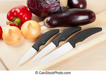 ceramic knifes with vegetables on cutting board