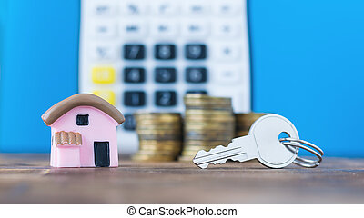 Ceramic model of a house with the coins and key on the background of the calculator.