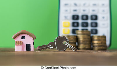 Ceramic model of a pink house with the coins and key on the background of the calculator.