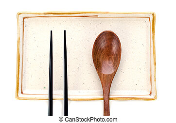 Ceramic Plate and chopsticks with wooden spoon ready for Asian food .