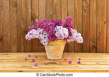 Ceramic pot with a branch of lilac flower on wooden background