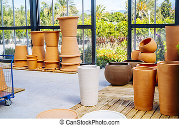 Ceramic pots for plants in a gardening shop. Outdoor plants and pots. Plant shop. Planting in ceramic pots. Gardening industry concept. High quality photo
