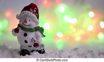 Ceramic smiling snowman figure in the snow, with shallow depth of field. Illuminated flashing garland defocused in the background. Colorful bokeh lights.