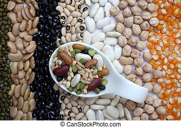 Ceramic spoon with mixed beans over seeds and grains background