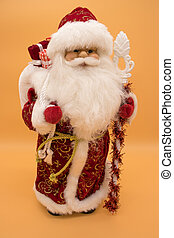 Ceramic statuette of Santa Claus in a red coat holding a staff isolated on yellow background