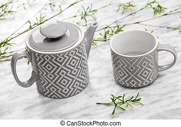 Ceramic teapot and cup on marble surface