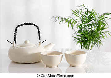 White ceramic teapot and cups on the table, with green plant in the background.