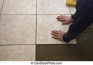 Ceramic Tile Installation - A man on his knees installing a ...