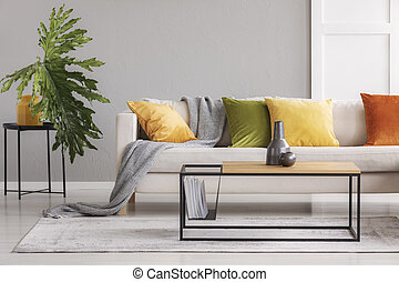 Ceramic vases on simple wooden coffee table in stylish living room with big comfortable couch with colorful pillows, real photo with copy space one the wall