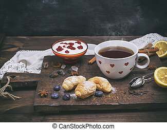 ceramic white cup with hot tea, croissants and yogurt