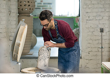 Ceramist Dressed in an Apron Placing Clay Sculpture in...
