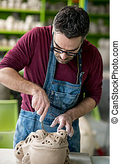 Ceramist Dressed in an Apron Sculpting Statue from Raw Clay...