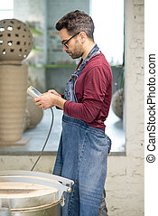Ceramist Dressed in an Apron Setting the Electric Oven for...