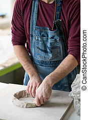 Ceramist Dressed in an Apron Working with Raw Clay in Bright Ceramic Workshop.