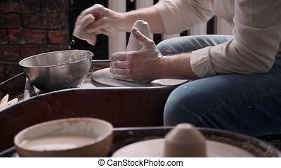 Ceramist person molding clay in small workshop studio. Specialist using spining wheel and sponge to make new shape on vase. He sitting inside cozy class room or work place with soft daylight inside
