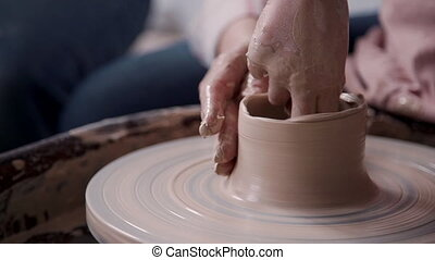 Ceramist person working with clay in pottery workshop studio...