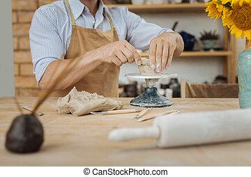 Ceramist using ceramics jigger standing near vase with...