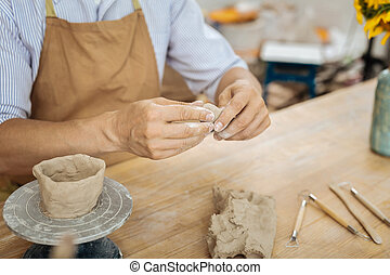 Ceramist wearing apron sitting at the table forming little...