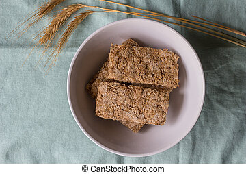 Cereal bars in breakfast bowl with wheat ears next to it