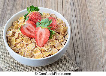 Cereal Conrflakes with strawberry on wood