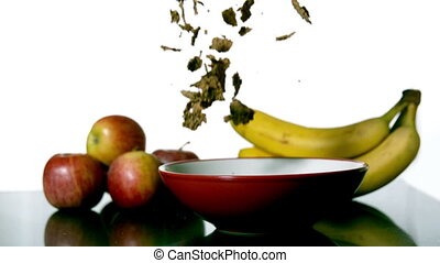 Cereal falling in a bowl beside fruit - Cereal falling in a...