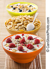 Fresh corn flakes with raspberries and milk close up