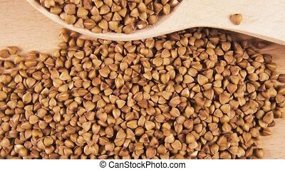 Cereal grain in wooden spoon on wooden background rotate...