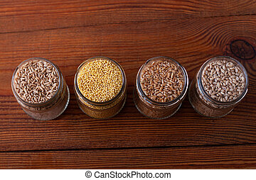 Cereal grains in glass jars on wooden background. Collection of different groats top view barley, oats, millet and wheat