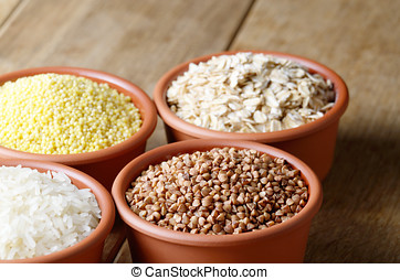 Cereal grains set in ceramic bowls on wooden table