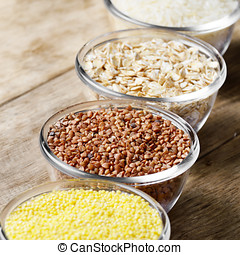 Cereal grains set in glass bowls on wooden table