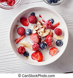Cereal muesli and sliced bananas, strawberries, berries, chopped almonds and walnuts with milk in a white ceramic bowl on white table. Top view.