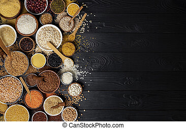 Cereals, grains, seeds and groats black wooden background