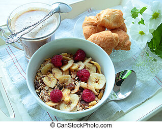 Cereals with berries and bananas for breakfast with cup of coffee